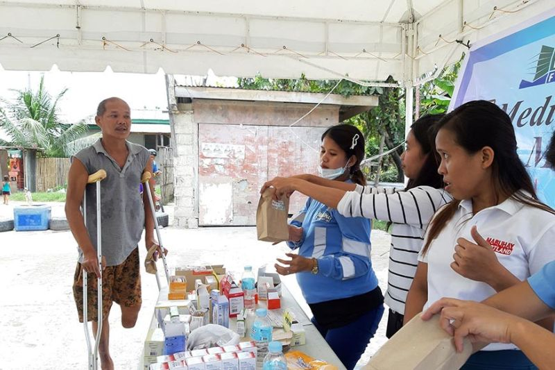CONCRETE KINDNESS. A person with disability receives vitamins from the volunteers of Mabuhay Filcement during its recent medical mission in Barangay South Poblacion, San Fernando, Cebu. (Contributed photo)