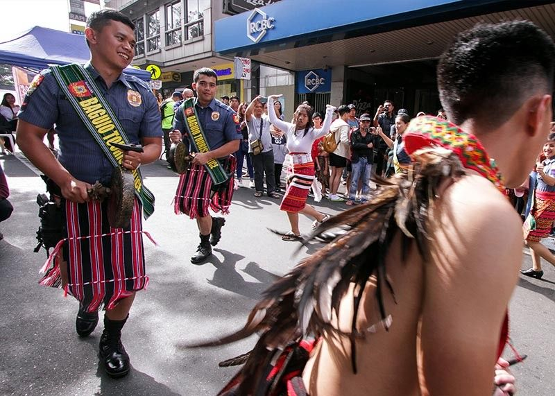 BAGUIO. Tourist cops, garbed in their ethnic attire, dance to the beat of the gong along Session Road in Baguio City on November 3, 2019. Indigenous Peoples games were also played on the same day in line with the celebration of the 7th Gong festival. (Jean Nicole Cortes)