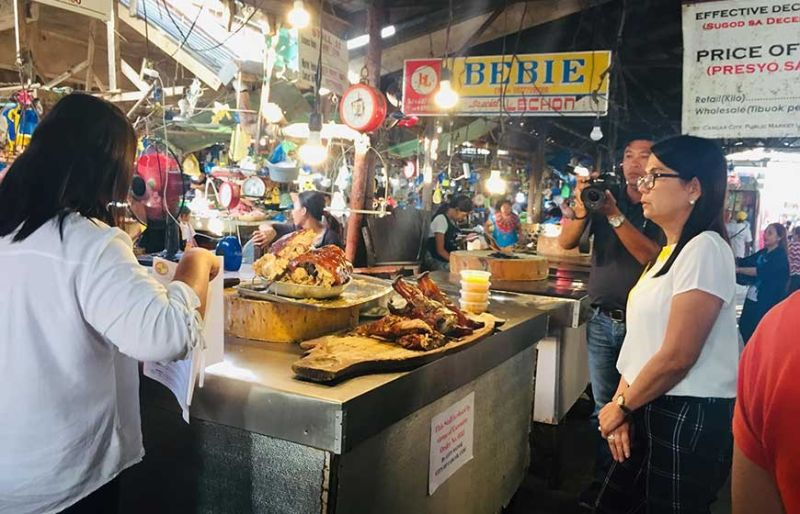 CLOSED. Carcar City Mayor Mercedita Apura (rightmost) visits the public market to close down four lechon stalls that have shortchanged their customers and have failed to secure permits. (Jonreil Traya)
