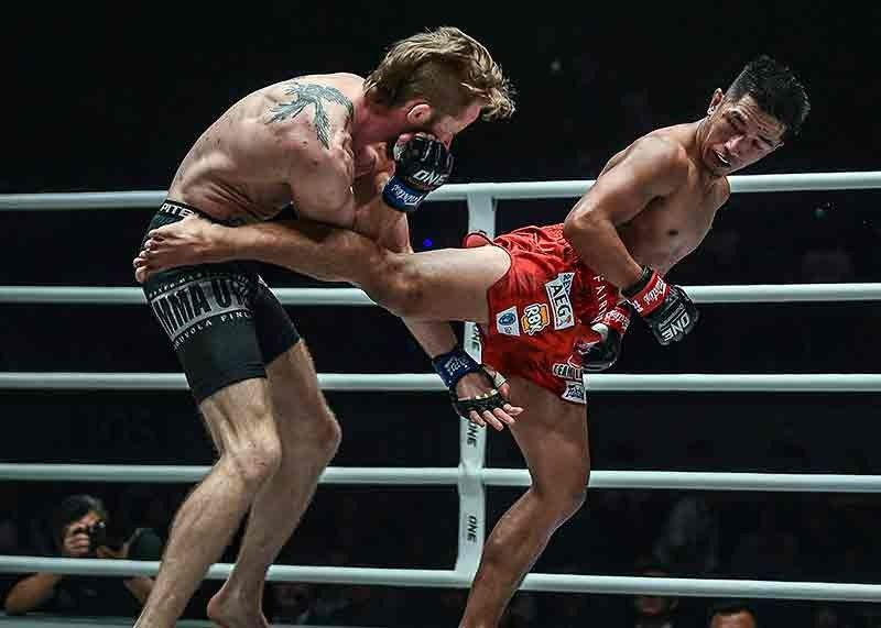 MANILA. Trademark. Geje Eustaquio connects with a spinning back against Toni Tauru in their flyweight contest. (ONE photo)