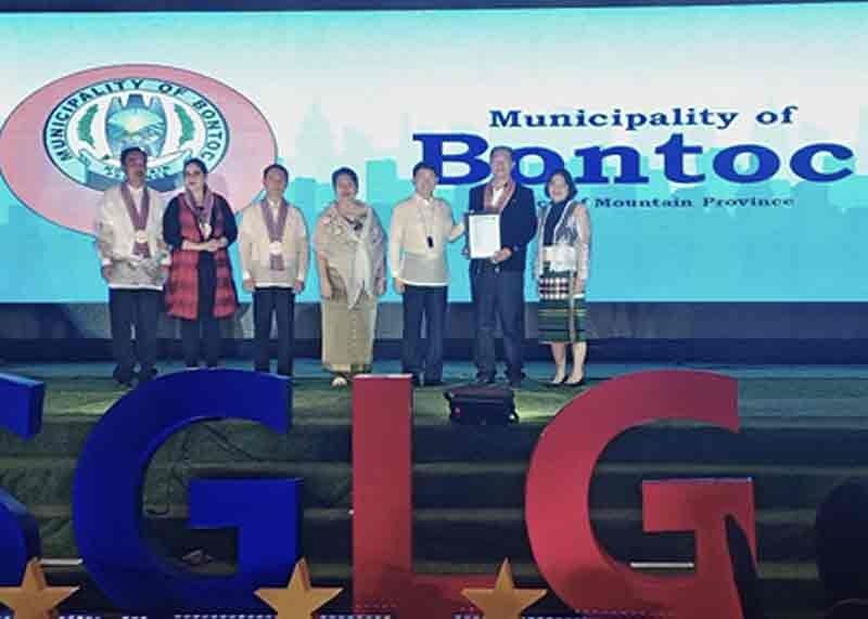 BONTOC. Mayor Franklin Odsey and Municipal Disaster Risk Reduction and Management Officer Johanna Padaen receive the award of the Municipality of Bontoc as 2019 National Seal of Good Local Governance (SGLG) Awardee on November 4, 2019. (Contributed Photo)