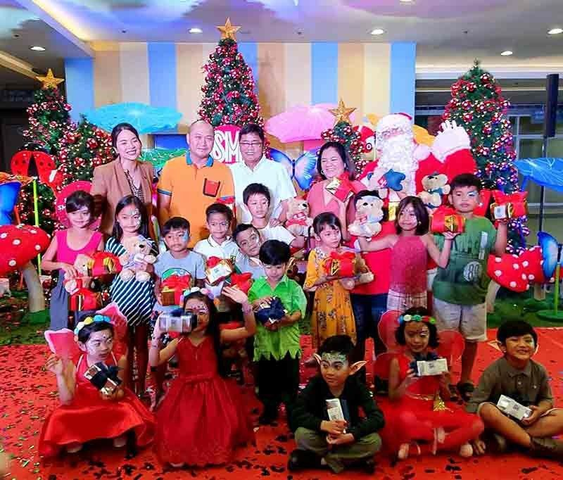 PAMPANGA. (From left) Andrea Madlangbayan, SM Supermalls Regional Operations manager-North 4; Councilor Celestino Dizon, Mayor Edwin Santiago and Mall Manager Lana Erroba give bears of joy to children during Sunday's Christmas centerpiece launching at SM City San Fernando Downtown. (Chris Navarro)