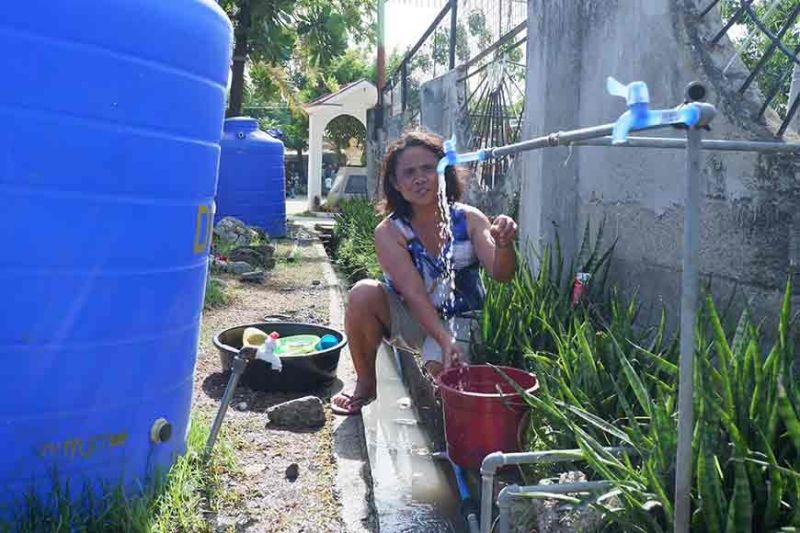 BENEFICIARY. Teresita Daligdig, 53, a housewife with two kids, was happy to find potable water supply provided by the water district within their temporary relocation site at the St. Arnold Janssen Chapel in Barangay San Nicolas, Cebu City. (Contributed Photo)