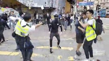 HONG KONG. In this image made from a video, a police officer (left) prepares to shoot a protester (center) in Hong Kong Monday, November 11. The police shot the protester as demonstrators blocked subway lines and roads during the Monday morning commute. (AP)