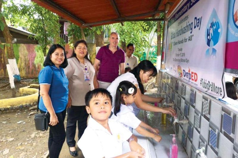 CLEAN HANDS. Vitens Evides International (VEI) project manager Patrick Egan (second from right, back row) joins Tisa Elementary School Principal Maricon Gumba (standing, center) and Metropolitan Cebu Water District Public Information Division manager Edna Inocando (in blue shirt) in teaching Tisa school kids on how to wash their hands properly during the Global Handwashing Day celebration on Oct. 15, 2019. (Contributed photo)