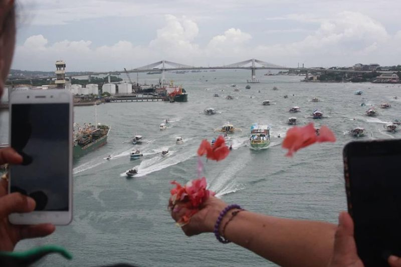 NOT SPARED. Devotees and workers of various Lapu-Lapu City barangays throw flowers and confetti as the seaborne procession for the feast of the Virgin of the Rule travels under the Mandaue-Mactan Bridge Tuesday, Nov. 12, 2019. Politics has marred what should have been a unifying celebration.  (SunStar photo / Allan Cuizon)