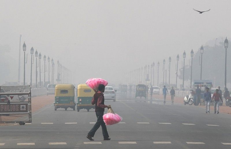 INDIA. A sweet candy vendor walks amidst thick layer of smog as he looks for customers in New Delhi, India, Tuesday, November 12. A thick haze of polluted air is hanging over India's capital, with authorities trying to tackle the problem by sprinkling water to settle dust and banning some construction. The air quality index exceeded 400, about eight times the recommended maximum. (AP)