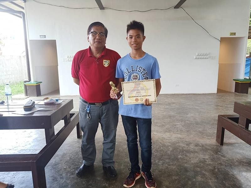 DAVAO. Central Mindanao University's Juan Ryu Bagonoc, right, receives the champion's trophy and certificate from tournament director Ronnie Tabudlong after topping the recently-concluded UM Open U-16 and Below Inter-School Invitational Chess Tournament held at the University of Mindanao Student Hub in Matina, Davao City. (Jhun Suter)