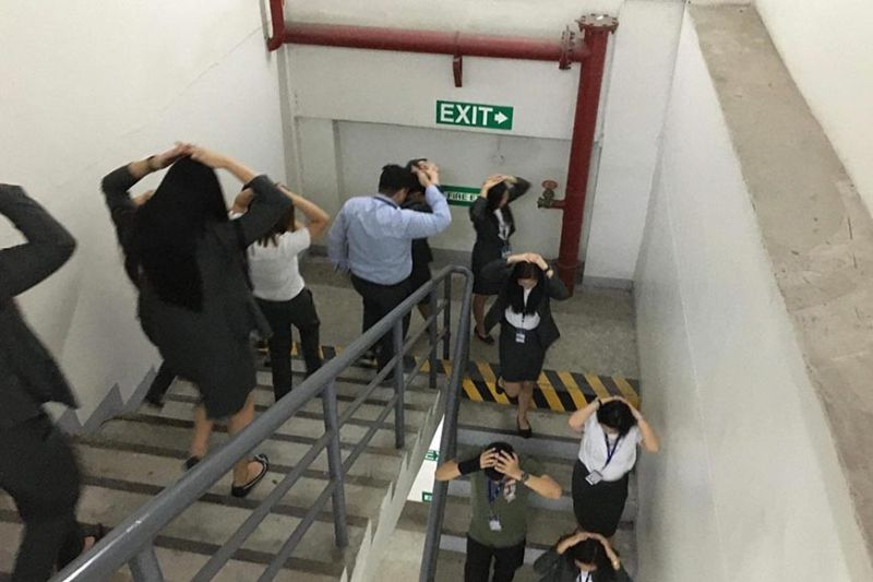 TARLAC. SM City Tarlac administration employees cover their heads while calmly exiting a building during the mall's earthquake drill on November 14. (Contributed photo)