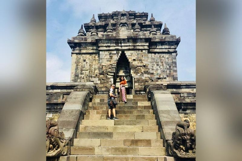Peterey and Anne Drew stand on the steps leading to Candi Mendut Temple.