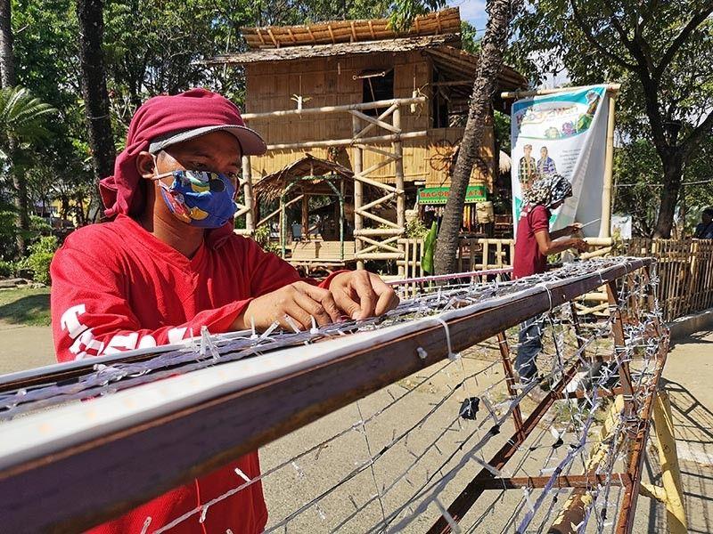 DAVAO. Gipaspasan na og pamutang sa mga trabahante sa Davao City Engineers Office ang mga Christmas lights sa gina-montar nga arko sulod sa Magsaysay Park alang sa pag-abli sa Pasko Fiesta sunod Biyernes. (Macky Lim)