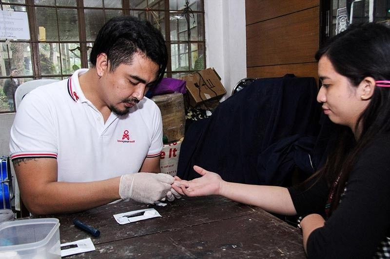 BAGUIO. I am Pogay 2014 grand winner and Mr. Gay World 2017 John Raspado takes a blood sample of a student during their HIV screening at the University of the Philippines campus on Saturday, November 16, 2019. Raspado is one of the HIV advocates under the Community-Based Screening Team-Baguio together with volunteers from the Metroplitan Community Church of Metro Baguio and Bahaghari advocacy group that promotes HIV awareness and urge the public to know their HIV status. (Jean Nicole Cortes)