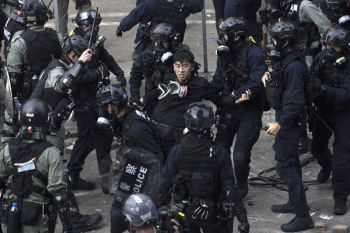 HONG KONG. Policemen in riot gear detain a protester who was trying to flee from the Hong Kong Polytechnic University in Hong Kong, Monday, November 18. Hong Kong police have swooped in with tear gas and batons as protesters who have taken over the university campus make an apparent last-ditch effort to escape arrest. (AP)