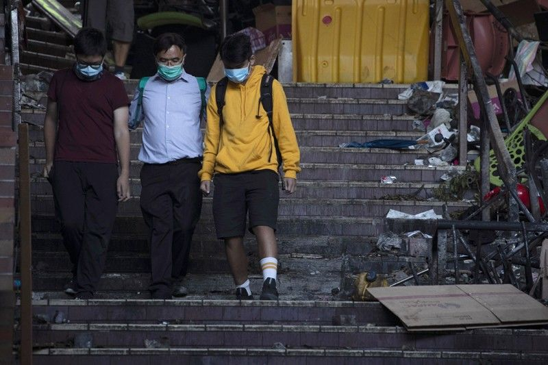 HONG KONG. A school principal (center) escorts two youths to surrender to the police at the Hong Kong Polytechnic University in Hong Kong on Tuesday, November 19. Police tightened their siege of the university campus where hundreds of protesters remained trapped overnight Tuesday in the latest dramatic episode in months of protests against growing Chinese control over the semi-autonomous city. (AP)