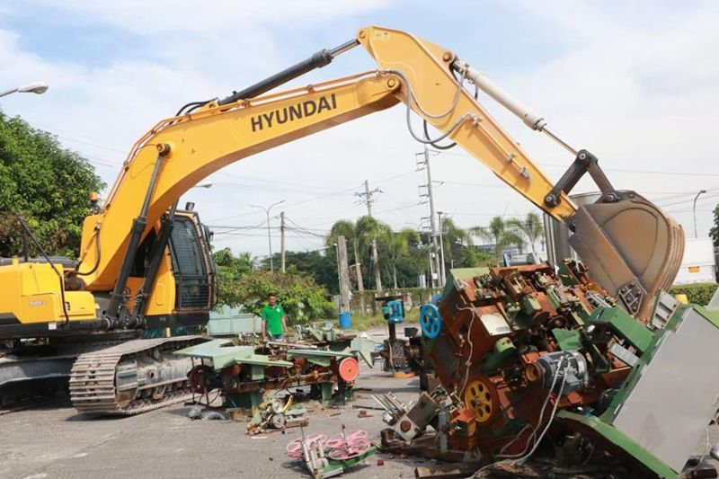 PAMPANGA. A backhoe from the Bureau of Customs-Port of Clark destroyed several units of smuggled cigarette manufacturing machines, counterfeit cigarette master cases and other packaging materials. (Chris Navarro)