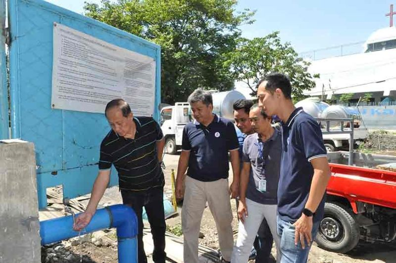 OPERATIONAL WELL. Metropolitan Cebu Water District acting general manager Stephen Yee (left) and Mactan Rock Industries Inc.'s (MRII) engineers check the supply from a water quality sampling point of MRII's facility in Barangay Tejero, Cebu City.  (Contributed Photo)