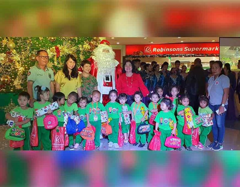 Bacolod City First Lady Elsa Leonardia leads the switch on of the 35-feet tall Christmas tree at the main Atrium of Robinsons Place Bacolod. With her are BJMP official SJO4 Jayson Baltazar, Marlene Sanogal, Cristine Tomas and Santa Clause. With the kids of Purok Carvic Day Care Center. (Photo by Carla N. Cañet)