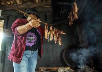 "BENGUET. A resident of Kabayan demonstrates how ""kinuday,"" a smoked meat is cooked at the Kabayan booth in the on-going agro–industrial fair of the Adivay Festival. All 13 municipalities of Benguet have their own booths at the Wangal Sports Complex. (Jean Nicole Cortes)"