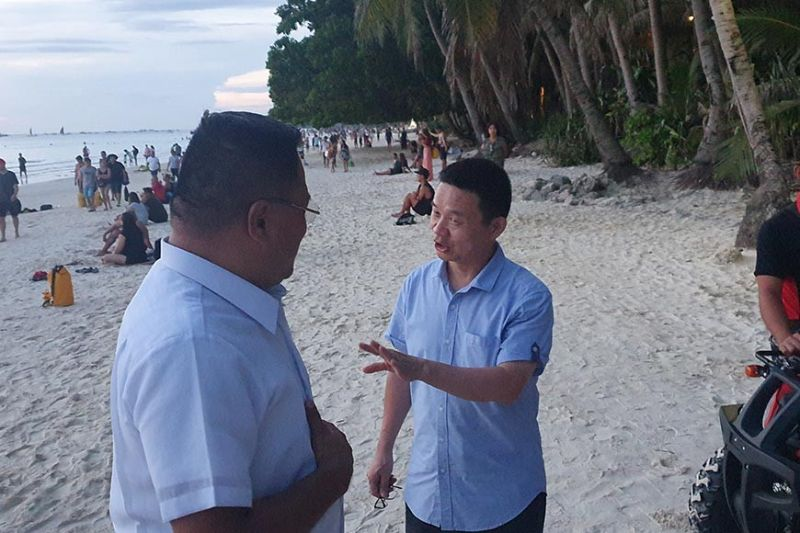 AKLAN. Chinese Embassy Consul General Lou Gang gives instructions to Peter Tay, liaison officer of the Chinese Embassy, on their visit to Boracay Island.
