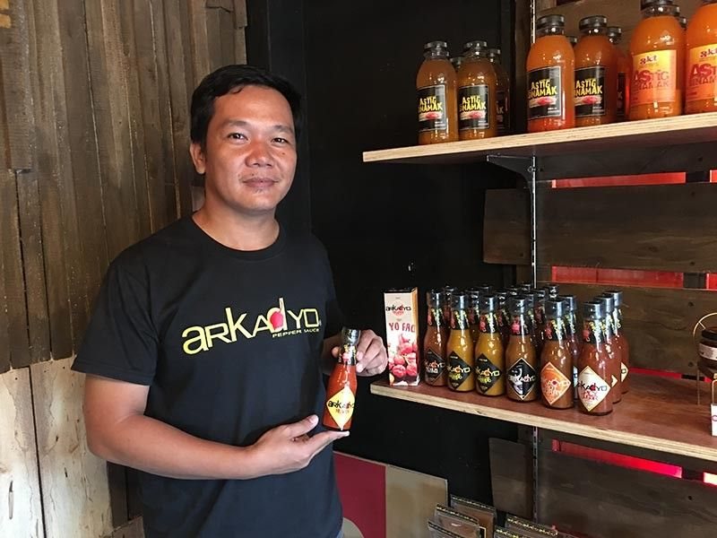 Arkadyo Pepper Sauce owner Russell Servillon posed with his flavored chili sauces at Dabawenyo Capsicum, a store he established who also housed other microbusinesses.