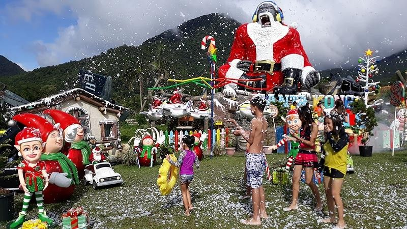 Local tourists enjoy the artificial snowflakes and ambiance of the grandest Christmas village at Campuestohan Highland Resort in Sitio Campuestohan, Barangay Cabatangan, Talisay City.