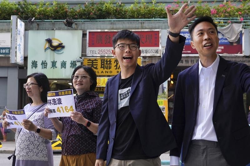 HONG KONG. Election winner candidate Kelvin Lam (right) and pro-democracy activist Joshua Wong (second right) wave to people and thank for their support, outside South Horizons Station in Hong Kong, Monday, November 25. Pro-democracy candidates won nearly half of the seats in Hong Kong's local elections, according to partial returns Monday, as voters sent a clear signal of support for the anti-government protests that rocked the Chinese territory for more than five months. (AP)