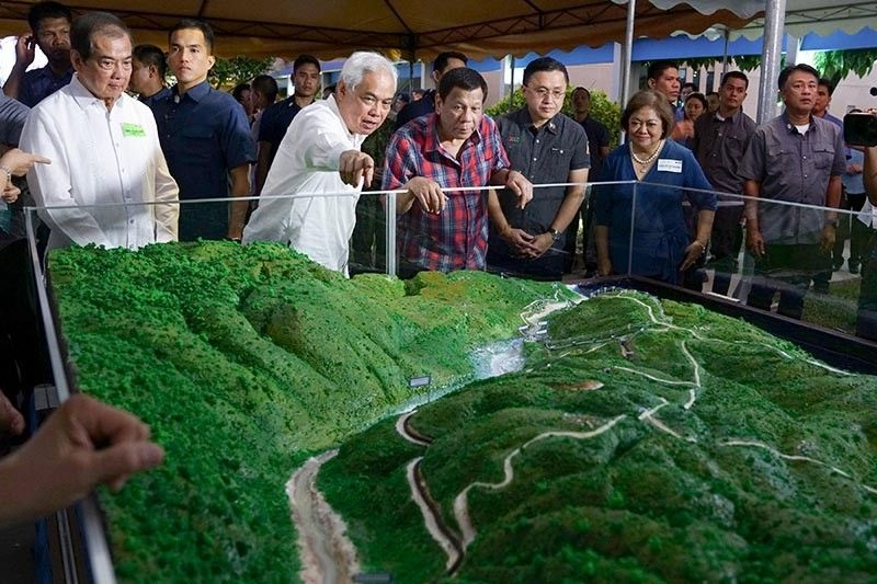INVESTING IN RENEWABLE ENERGY. Alsons Consolidated Resources, Inc. (ACR) Director Nicasio Alcantara showa to President Rodrigo Duterte the scale model of the Siguil Hydro Power Corporation's 14.5-Megawatt Hydropower Project during its launch in Maasim, Sarangani Province on November 22, 2019. Also in photo are ACR chairman Tomas I. Alcantara, Senator Christopher Lawrence Go, and Energy Regulatory Commission chairperson Agnes VST Devanadera. (Joey Dalumpines, Presidential photo)