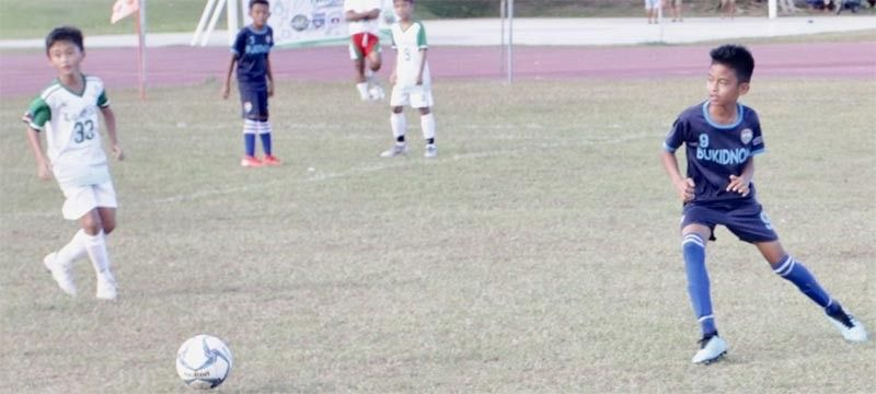 TARLAC. Bukidnon defender Jimm Fabela (right) waits to whip the ball to the goal as One La Salle's Paulino Tobias watches during the Luzon Cup championship match in Tarlac. (Jack Biantan)