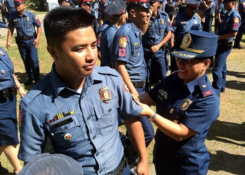 BAGUIO. Police Corporal Jaynus Puno from the Police Regional Office-Cordillera Public Information Office is assisted by Police Major Carolina Lacuata, head of the PIO, in the promotion and donning of ranks of 1,149 police officers and personnel at Camp Bado Dangwa in la Trinidad, Benguet. (Jonathan Llanes)