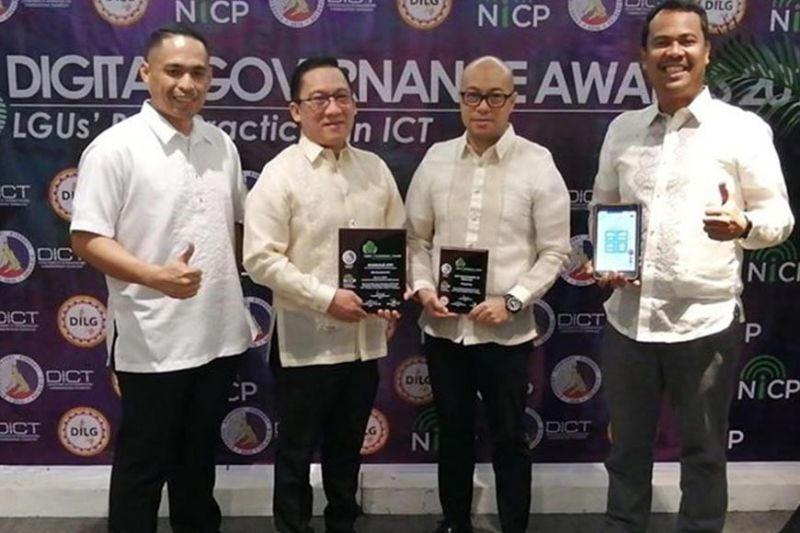 AWARDS. Mandaue City Mayor Jonas C. Cortes (second from left) holds the eGov Customer Empowerment Award while City Administrator Jamaal James Calipayan (third from left) bears the citation as eGov finalist. The awards recognize best practices among local government units in the field of information and communications technology. With them are John Eddu Ibañez (left), Cortes's chief of staff, and Cloyd B. Dedicatoria, Guardian creator and SugboTek Inc. officer with his high-precision tab now used by the City's emergency responders. (Contributed photo)