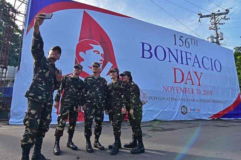 DAVAO. Nagpahulagway ang mga sakop sa Tactical Operations Wing Eastern Mindanao sa Philippine Air Force atubangan sa dakong tarpaulin nga gimuntar kilid sa Bonifacio Rotunda kagahapon atol sa pagsaulog sa 156th Bonifacio Day sa Davao city kagahapon. MACKY LIM