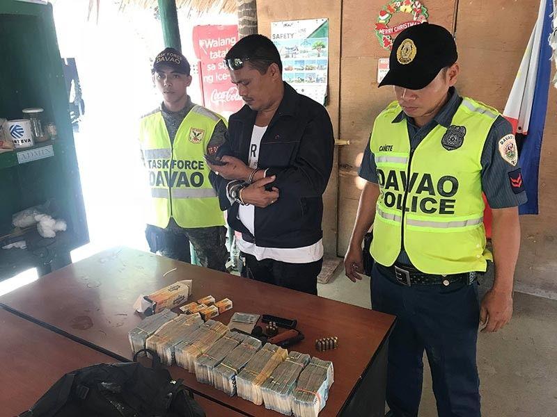 DAVAO. Ang suspek gihulagwayan uban sa mga binandol nga kuwarta, mga bala ug armas ang nakuha sud sa iyang sakyanan. (Hulagway sa Bunawan Police Station)