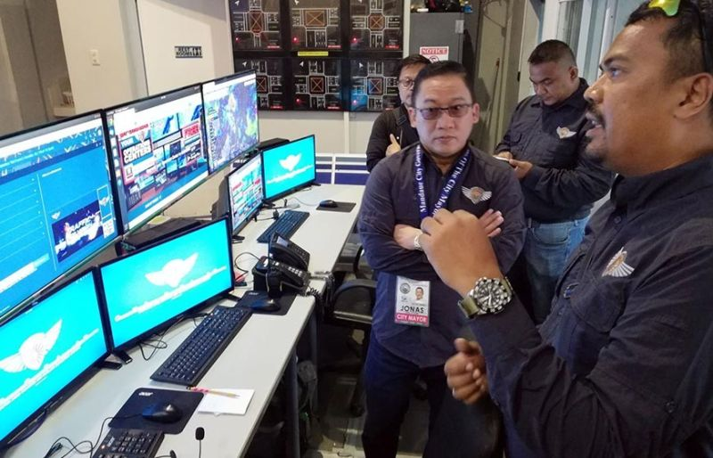 GUARDIAN: Gipakita ni SugboTek CEO Cloyd B. Dedicatoria (tuo) si Mandaue City Mayor Jonas C. Cortes sa operasyon sa Guardian Command and Control for Emergency Response sulod sa Bantay Mandaue 161 Operation Center. (Tampo nga hulagway)