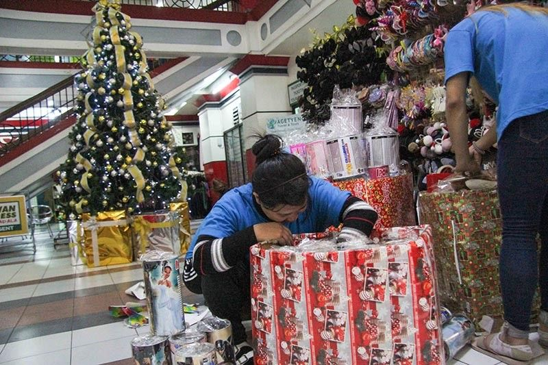 BAGUIO. In the spirit of Christmas, sales ladies cover some of their boxes with Christmas gift wrappers as decoration this yuletide season. (Photo by Jean Nicole Cortes)