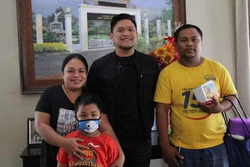 HOPE IN CUPS. Talisay City, Cebu Mayor Gerald Anthony Gullas Jr. (center) poses with the family of eight-year-old Resh Nathan Formentera (wearing face mask), who is battling acute lymphoblastic leukemia (a type of cancer of the blood and bone marrow). The boy's parents are selling cups worth P300 each to raise funds for his three chemotherapy sessions. (SunStar photo / Fe Marie Dumaboc)