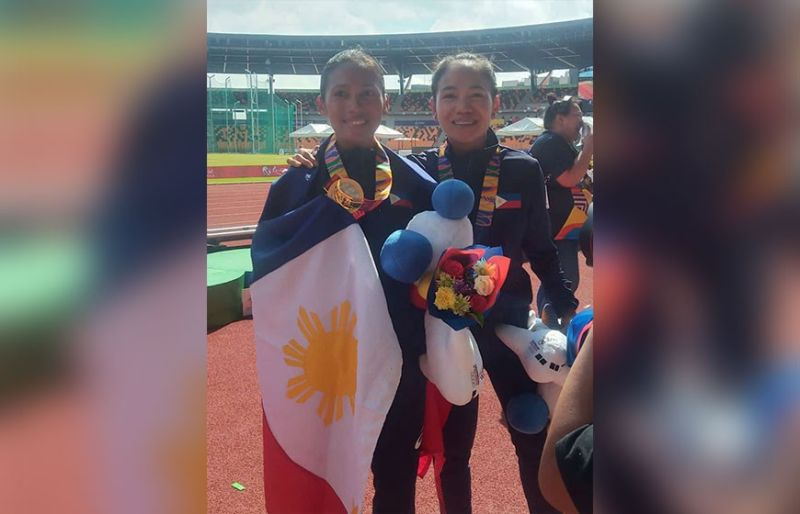 LUCKY BREAK. Christine Hallasgo (left) and Mary Joy Tabal celebrate after a 1-2 finish in the women's marathon. The two were running second and third before the leading Indonesian runner collapsed in the final 400 meters. (SunStar photo/Richiel S. Chavez)