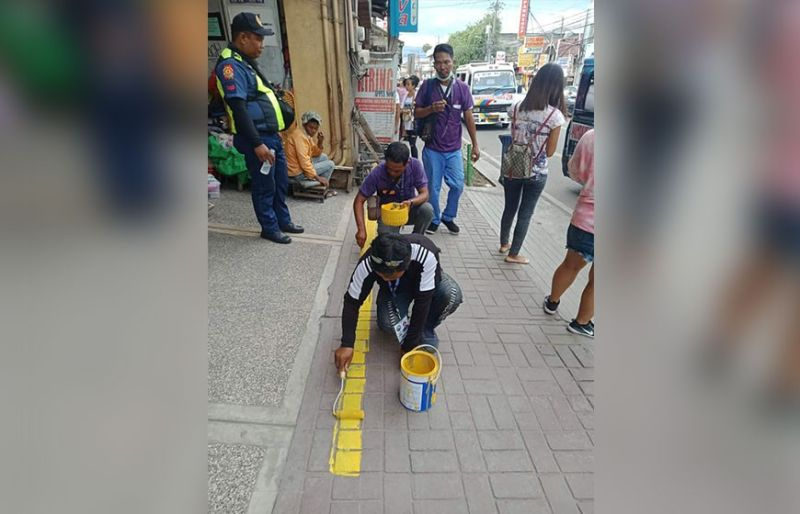 OFF-LIMITS. Mandaue City Hall personnel make a demarcation line to indicate the portion of the sidewalk that should be free of any obstruction. (Photo/Mandaue City Legal Office-Enforcement Unit)