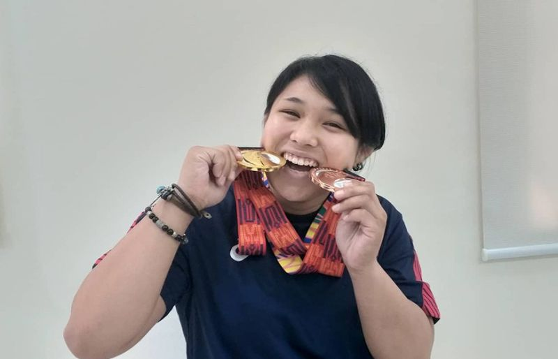 "ALL SMILES. Mariya Takahashi, who defended her judo gold medal and added a women's team bronze in the 30th SEA Games, beams as she poses with her medals after paying a courtesy visit to Philippine Sports Commission (PSC) Chairman William ""Butch"" Ramirez at the latter's office in Manila yesterday, December 9. (Marianne L. Saberon-Abalayan)"