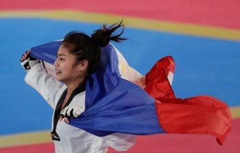ANOTHER ONE. Pauline Lopez celebrates with the flag after beating Cambodia's Aliza Chhoeung in the women's -Under 57 kilos Taekwondo final. (AP photo)