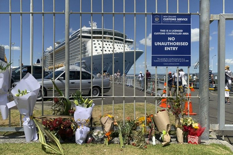 NEW ZEALAND. Flowers are laid on makeshift memorial in front of cruise ship Ovation of the Seas, in Tauranga, New Zealand, Tuesday, December 10. A volcanic island in New Zealand erupted on Monday, December 9, in a tower of ash and steam while dozens of tourists were exploring the moon-like surface, killing multiple people and leaving many more missing. (AP)