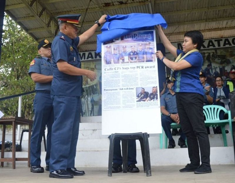"BACOLOD. Negros Occidental Police Provincial Office (Nocppo) Director Police Colonel Romeo Baleros (left) and Easter Anne Doza (right) of the Philippine Information Agency lead the unveiling of the official newsletter ""Ang Pahayag"" during the flag raising ceremony held at the headquarters' parade ground in Bacolod City on Monday, December 9. (Teresa D. Ellera)"