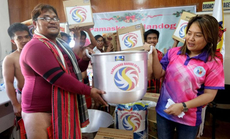 HANDOG SA IP. Philippine Charity Sweepstakes Office-General Manager Royena Marzan Garma distributes kitchen equipment and other food packs to 10 tribes of the Cordillera to be used on occasions and gatherings, during the Pamaskong Handog ng PCSO on Sunday in Baguio City. (Photo by Zaldy Comanda)