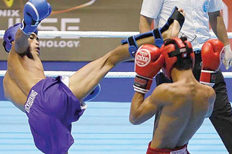 CORDILLERA PRIDE. Jomar Balangui (in blue) connects against Khem Chann of Cambodia during their bout in kickboxing of the 30th Southeast Asian Games. (Phisgoc photo)