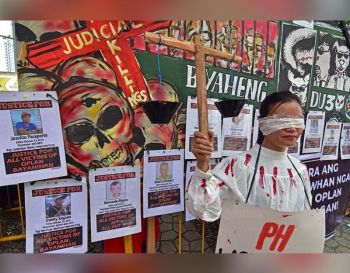 "DAVAO. Miposing ang babaye isip ""Lady Justice"" atubangan sa mga hulagway sa mga nangamatay nga aktibista atol sa rali sa nagkadaiyang progresibong pundok kagahapon sa Freedom Park, Roxas Avenue, Davao City atol sa ika-71 nga International Human Rights Day. (Macky Lim)"