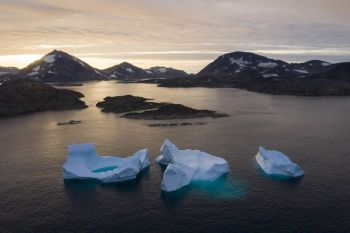 FILE - In this Aug. 16, 2019, file photo, large icebergs float away as the sun rises near Kulusuk, Greenland. Rising temperatures and diminished snow and ice cover in the Arctic are imperiling ecosystems, fisheries and local cultures, according to a report issued Tuesday, Dec. 10 by the National Oceanic and Atmospheric Administration.  (AP Photo/Felipe Dana, File)
