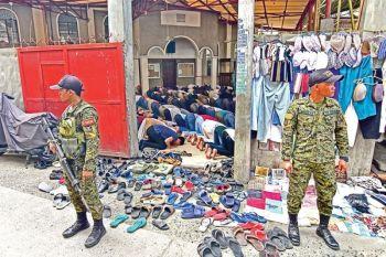 DAVAO. Mga sakop sa Task Force Davao nagbarog gawas sa Mosque sa Barangay 23-C Isla Verde Biyernes, Disyembre 13, aron nga bantayan ang palibot sa lugar atol sa gihimong pag-ampo niadtong Biyernes sa udto. (Macky Lim)