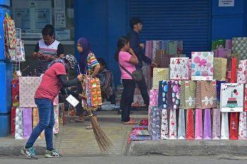 DAVAO. Gisilhigan sa sweeper sa Davao City Environment and Natural Resources Office (Cenro) ang atubangan sa nagtapun-og nga paperbag nga gibaligya sa mga vendors sa San Pedro Street, ning siyudad, niadtong Sabado, Disyembre 14. (Macky Lim)