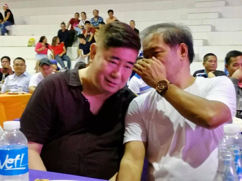 """CAGAYAN DE ORO. Gingoog City Vice-Mayor Peter Unabia whispers to former Agriculture undersecretary Jose Gabriel """"Pompee"""" La Viña during the Christmas party of the Padayon Pilipino and allied political groups at the Nazareth gymnasium in Cagayan de Oro City, Tuesday, December 10. (Photo courtesy of Pompee La Viña Facebook)"""