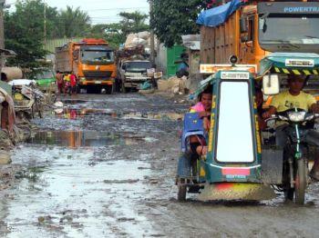 BAD ROADS. The potholes and often muddy roads in Barangay Inayawan, Cebu City have been blamed on  heavy trucks that pass the area. (SUNSTAR FOTO / ALLAN CUIZON)