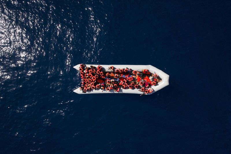 """LIBYA. In this Sunday, May 6, 2018 file photo, refugees and migrants wait to be rescued by members of the Spanish non-government organization Proactiva Open Arms, after leaving Libya trying to reach European soil aboard an overcrowded rubber boat, north of Libyan coast. The United Nations (UN) is urging governments, businesses and others to """"reboot"""
